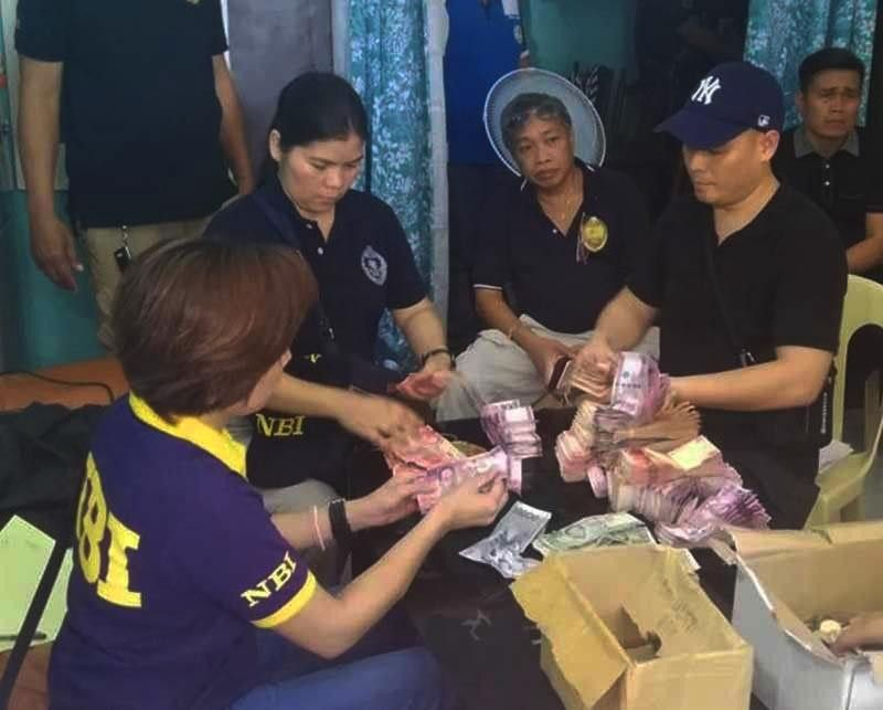 MISAMIS. In this photo taken on June 10, 2019, National Bureau of Investigation (NBI) agents count bills found in a Kapa office. (SunStar Cagayan de Oro Photo)