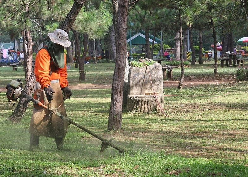 BAGUIO. A worker cuts growing weeds at the Burnham Park in order to maintain the cleanliness and beauty of the park for the public to enjoy. (Photo by Jean Nicole Cortes)