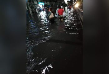 WET WALK. Many passengers braved the rain and the water that inundated the highway in Barangay Bulacao, Talisay City to get home last Friday night, June 14. Drivers of public utility vehicles had opted to wait for the water level to go down. (Contributed Photo)