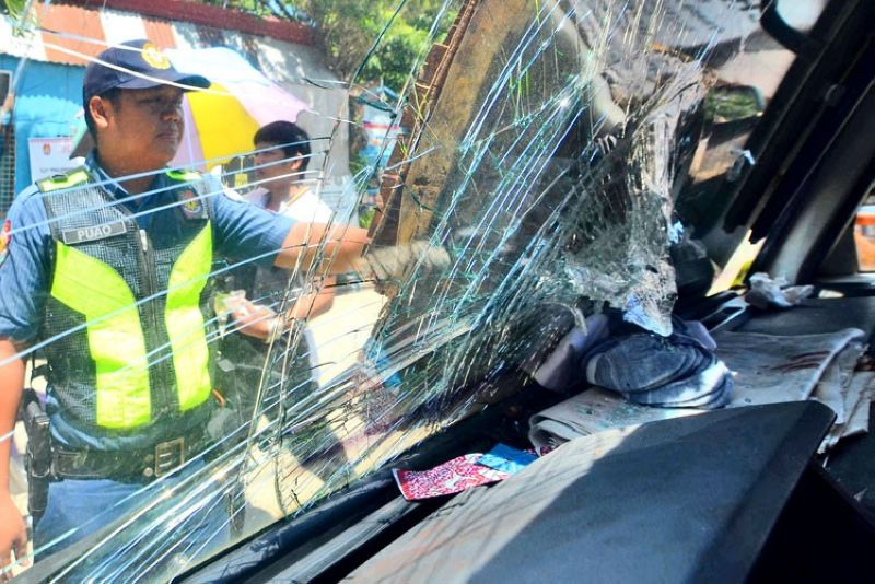 CEBU. A policeman examines the broken windshield of the truck owned by murdered Chinese national Yi Feng Guo Yang. Yang, 51, was driving his truck with his two kids when unidentified men onboard motorcycles ambushed them in Barangay Cubacub, Mandaue City on the evening of Father's Day, June 16. Police believed the ambush may have been related to Yang's business dealings. (SunStar photo/ Alan Tangcawan)