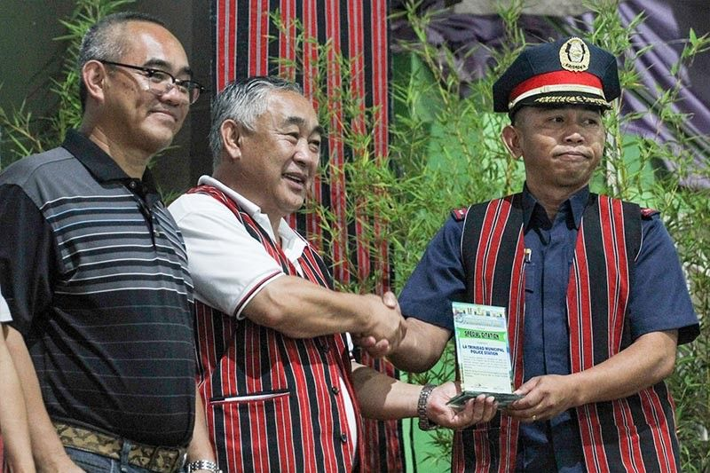 BENGUET. La Trinidad Mayor Romeo Salda and Vice Mayor Joey Marrero award a plaque of citation to former chief of police Benson Macli-ing during the celebration of the town's Foundation Day on June 14, 2019. (Jean Nicole Cortes)