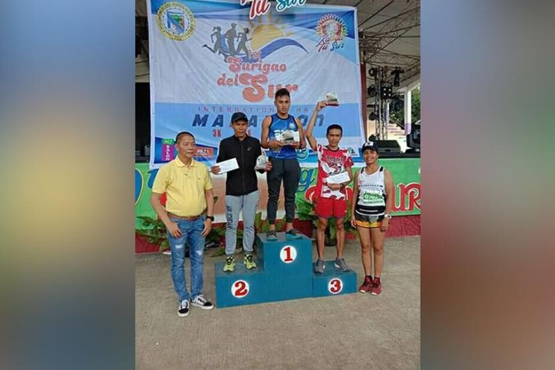 DAVAO. Rizal Memorial Colleges (RMC) varsity scholar Arlan Arbois, Jr., center, receives his champion's plaque and cash prize in the 1st Surigao del Sur International Half Marathon Sunday. (Contributed Photo)