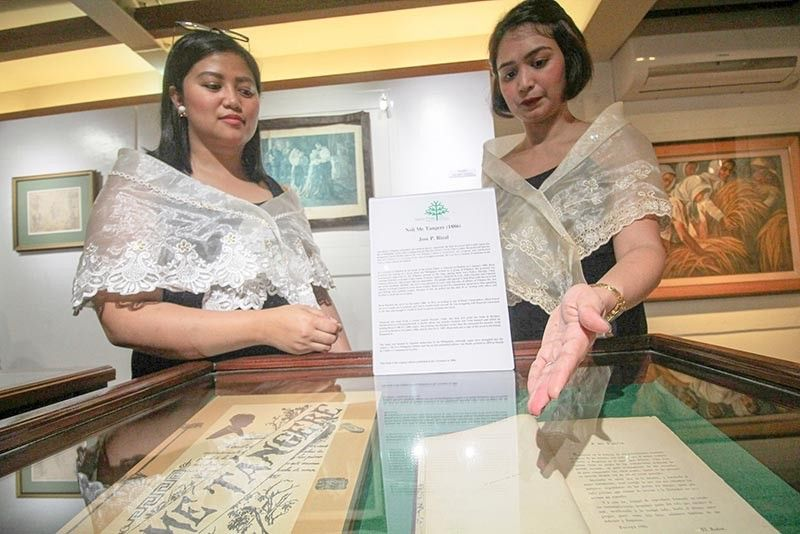 BAGUIO. Hotel workers Johanna Lopez and Noof Castro show Dr. Jose Rizal's original edition and replica of the book Noli Me Tangere displayed at the Adkos Gallery  where 10 of Rizal's artifacts are on display. The gallery is open for free daily. (Photo by Jean Nicole Cortes)