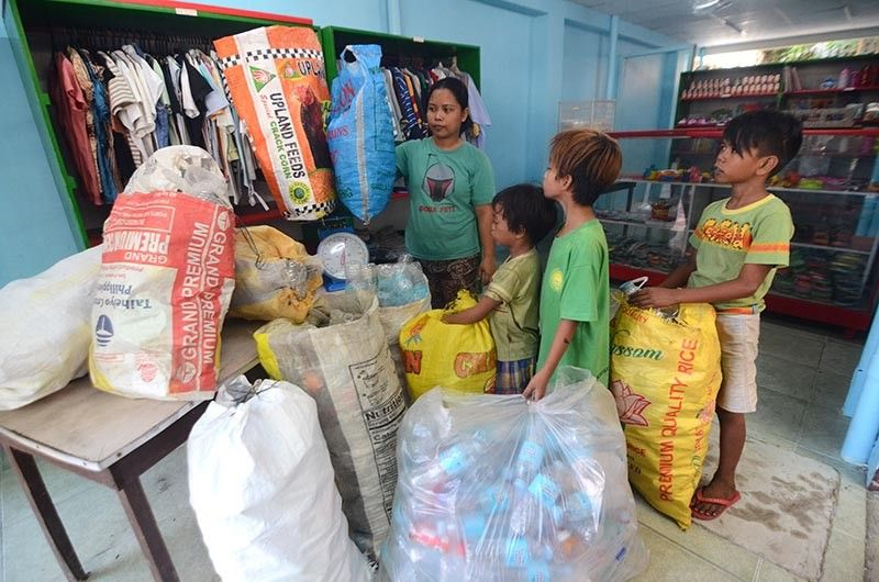 PRICELESS. Children turn in their sacks containing plastics to the employee of Plastic Barter Store in Barangay Mabini, Cebu City in exchange for food or toys. (SunStar photo / Alan Tangcawan)
