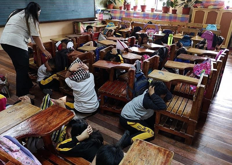 BAGUIO. A teacher and pupils of Dominican Elementary School in Baguio City participate in a safe and orderly execution of an earthquake drill. The city suffered an earthquake in July 16, 1990 measuring 7.9 in the Richter scale killing scores and rendering major damages to infrastructure. (Photo by Dave Leprozo Jr.)