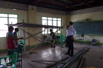 BACOLOD. Bacolod City Councilor Renecito Novero, chairperson of the city council committee on education, inspect the classroom ceiling at Domingo Lacson National High School that collapsed on Tuesday, June 18, 2019. (Contributed photo)