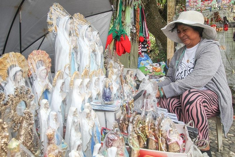 BAGUIO. Julie Dicang, 61, sells religious items at the Lourdes Grotto stairs since moving to Baguio City in 1976. Dicang was able to put her three children to school through her business. (Jean Nicole Cortes)