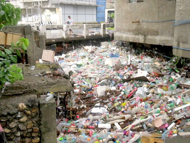 FLOATING GARBAGE clogged up the Mahiga Creek under the Subangdaku bridge in Mandaue City during yesterday afternoon's rain. When the water level rose, the garbage flowed out into the streets. (SUNSTAR FOTO / ALLAN CUIZON)