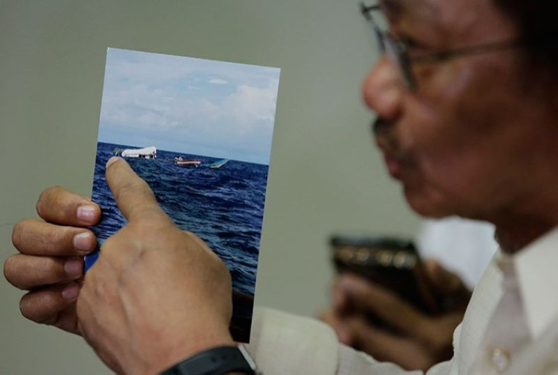 MANILA. Department of Agriculture Secretary Emmanuel Piñol shows a June 10 photo of the damaged Filipino fishing boat F/B Gimver 1 after it was hit by a Chinese vessel at the Recto bank during a press conference in Manila on June 17, 2019. (AP)