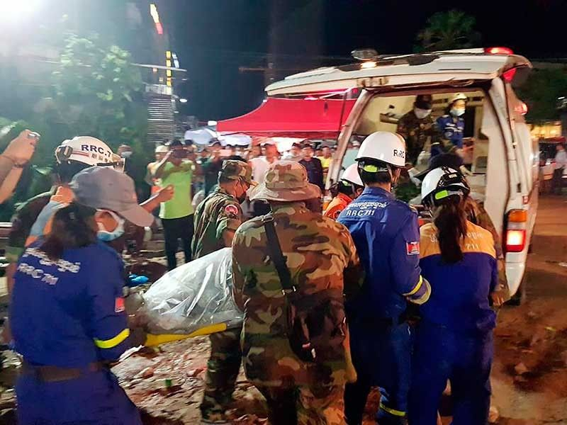 CAMBODIA. In this Sunday, June 23, 2019, photo provided by Preah Sihanouk provincial authorities, rescuers enter a victim body onto an ambulance at a site of a collapse in Preah Sihanouk province, Cambodia. Rescuers on Monday were continuing to search the rubble of a building that collapsed while under construction in a Cambodia beach town, killing dozens of workers as they slept in the unfinished condominium that was doubling as their housing. (Preah Sihanouk provincial authorities via AP)