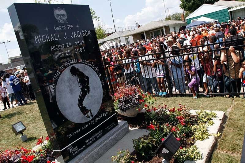 INDIANA. In this June 25, 2010 file photo, Michael Jackson fans gather around a monument that was unveiled in Gary, Ind., on the first anniversary of the pop icon's death. As the 10th anniversary of Jackson's death approaches, experts say his music legacy is still going strong despite the documentary's detailed abuse allegations. (AP File)