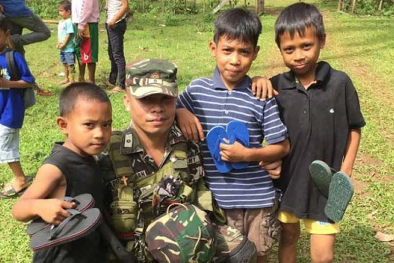 "LEYTE. Army Major Arturo Dumalagan spends time with the recipients of the ""Tsinelas Para Sa Kapayapaan"" project. (Contributed photo)"