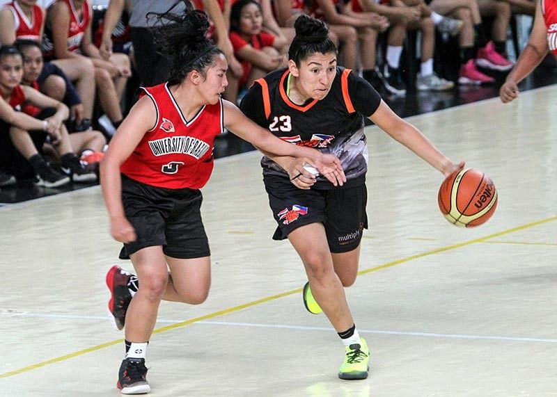 BAGUIO. Viviana Vasquez of Action Basketball drives hard against a University of Baguio Lady Cardinals defender during a friendly game last week. The foreign team last visited Baguio City two years ago to share their ministry through sports. (Photo by Jean Nicole Cortes)