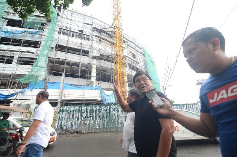 INSPECTION: Si Cebu City incoming Mayor Edgardo Labella (wala) nga gi-interview ni Superbalita Cebu reporter Philip Cerojano (tuo) sa dayon niyang pagsulod sa padayong gitrabaho nga 10 ka andanang Cebu City Medical Center (CCMC). Nakurat si Labella human makita ang kahimtang sa sud sa edipisyo nga di pa magamit ning tuiga. (Alan Tangcawan)