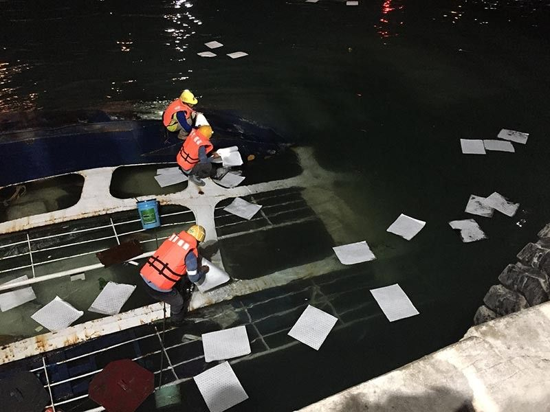 PREVENTING OIL SPILL. The personnel of Solid Earth Development Corp. place absorbent pads on the parts of the capsized mv Eva Mary Grace where oil spots were noticed around 8:30 p.m. on Tuesday, June 25, 2019. (Contributed photo / Cerwin Eviota)