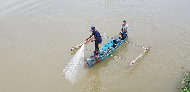 CAGAYAN DE ORO. A fisherman and his companion pull a net from the banks of Cagayan River. Despite potential risk of flashflood during rainy season, residents living along the riverbanks continue to rely on the river for their daily food consumption. (Nef Luczon)