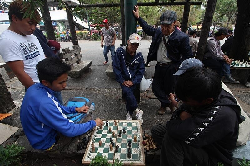 BAGUIO. People from different walks of life battle it out in a chess game at the Igorot Park in Baguio City. (Photo by Jean Nicole Cortes)