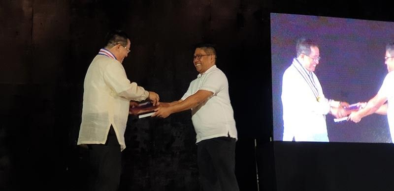 "NEGROS. Dino Jose Maria Orceo Acuna presents a book entitled ""Simple Life Principles"" that he wrote to Mayor Palanca. His book is about love, perseverance, family and friends, the beauty of life, God's plan for us, reality and destiny. (Contributed photo)"