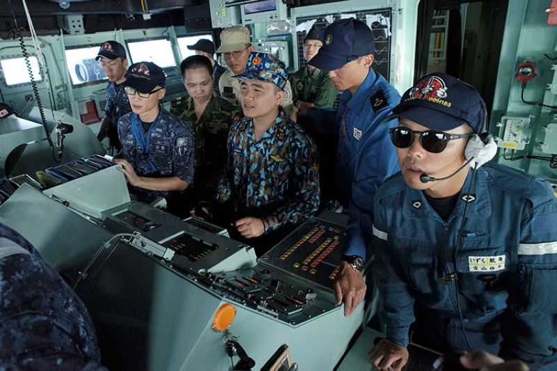 BRUNEI. In this June 26, 2019, photo, Vietnam navy lieutenant Le Huu Hai (center) steers the wheel of Japan's Maritime Self-Defense Force helicopter carrier JS Izumo (DDH-183) during a ship maneuvering training session alongside Japanese officers off the coast of Brunei. (AP)