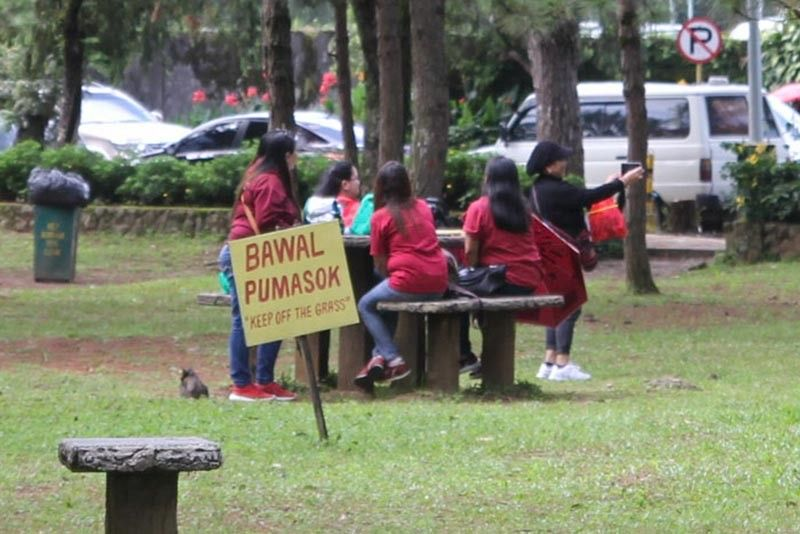 """BAGUIO. A group ignores the huge poster at the Burnham Park warning people to """"keep off the grass"""". (Photo by Jean Nicole Cortes)"""