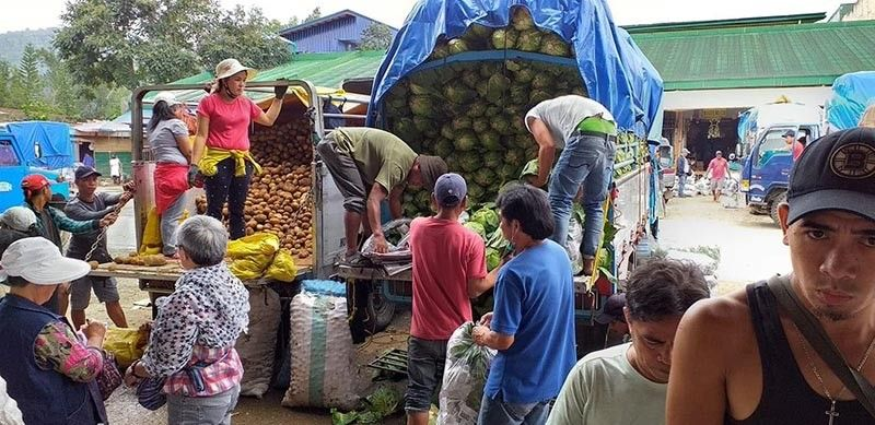 BENGUET. Farmers unload and pack vegetables at the La Trinidad Trading Post in Benguet. (Photo by Aira Quiliza/UC Intern)