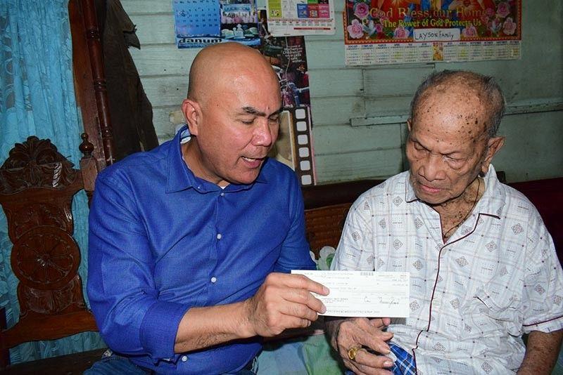 Mabalacat City Mayor Cris Garbo hands a P100,000 check to centenariam Guillermo Layson of Barangay Poblacion.(Contributed Photo)