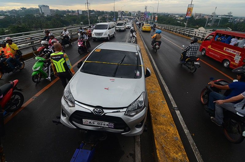 SUICIDE? A traffic enforcer mans the traffic near  the vehicle of businessman Roland Digamon Tacgos on Marcelo Fernan Bridge. Tacgos reportedly took his own life on Tuesday dawn, July 9, 2019 over financial woes. (SunStar Photo/Alan Tangcawan)