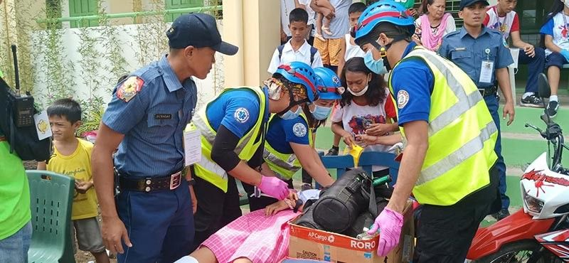 QUICK RESPONSE. Emergency responders attend to a Crossing Bayabas National High School student who was among the 145 students who experienced dizziness and nausea while others even lost consciousness while being evacuated due to aftershocks in Toril, Davao City on Wednesday, July 10. (Photo by Janoz Laquihon)