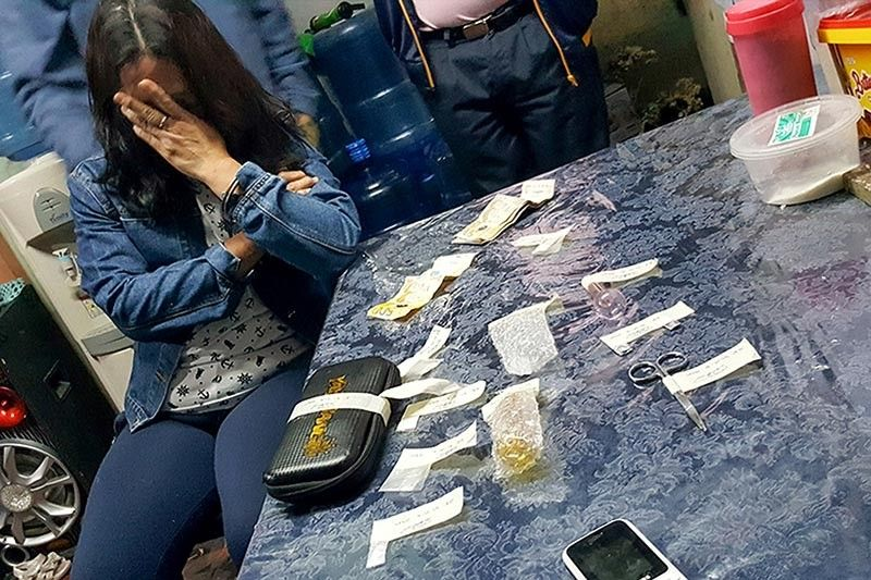 BAGUIO. Authorities collect evidence from a 25-year-old woman who was caught during a drug bust on July 10, 2019 in Purok 25, Irisan, Baguio City. (Jean Nicole Cortes)