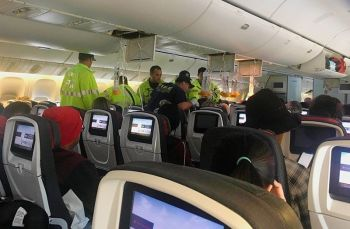 """In this photo provided by Hurricane Fall, responders treat a passenger on an Air Canada flight to Australia that was diverted and landed at Daniel K. Inouye International Airport in Honolulu on Thursday, July 11, 2019. The flight from Vancouver to Sydney encountered """"un-forecasted and sudden turbulence,"""" about two hours past Hawaii when the plane diverted to Honolulu, Air Canada spokeswoman Angela Mah said in a statement. (AP)"""