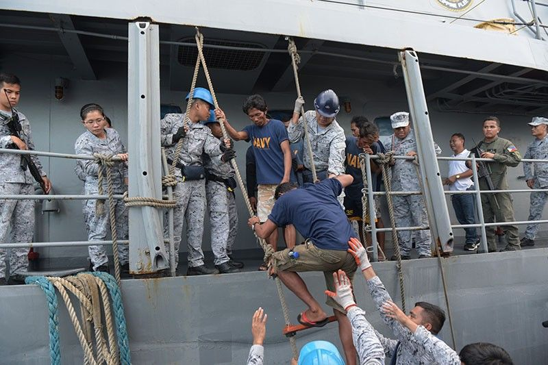 In this June 14, 2019, file photo, rescued Filipino fishermen are transferred to another ship as they head back to shore in Occidental Mindoro province, Philippines, after sinking of their fishing boat by a Chinese trawler in the South China Sea. In a meeting of the Association of Southeast Asian Nations' defense chiefs, Philippine Defense Secretary Delfin Lorenzana thanked the Vietnamese captain whose boat rescued the 22 Filipino fishermen. (AP file photo)
