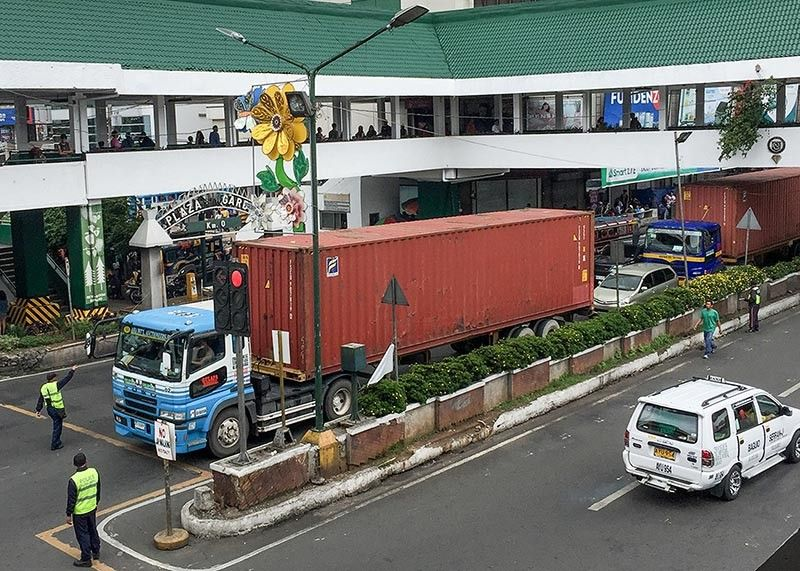 BAGUIO. Traffic enforcers stop three cargo trucks along Harrison Road on Sunday, July 14, for violating the truck ban at the Central Business District from 6 a.m. to 9 p.m. Baguio City is currently looking ways to help improve the traffic condition with the help of experts from MMDA. (Photo by Jean Nicole Cortes)