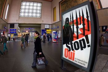 SWITZERLAND. In this November 4, 2009, file photo, people walk by a poster from the right-wing Swiss People's Party depicting a woman wearing a burqa in front of a Swiss flag upon which are minarets which resemble missiles, at the central station in Geneva, Switzerland. Later in the month, a successful referendum banned the construction of new minarets in the country. (AP)