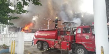 CAGAYAN DE ORO. A fireman stands on top of a firetruck on Monday attempting to extinguish the fire that set ablaze in Macabalan's Piaping Puti community just beside the Philippine Ports Authority complex where at that time, government officials and guests are present during the inaugural opening of the country's biggest passenger terminal. (PJ ORIAS)