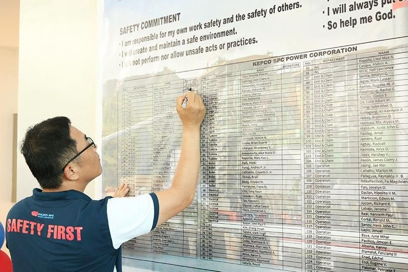 SUBSCRIBING TO SAFETY. An employee of Kepco SPC Power Corp. affixes his signature on the safety commitment wall, a symbolic move that encourages himself and his fellow employees to adhere to safety measures of the company. (Contributed photo)