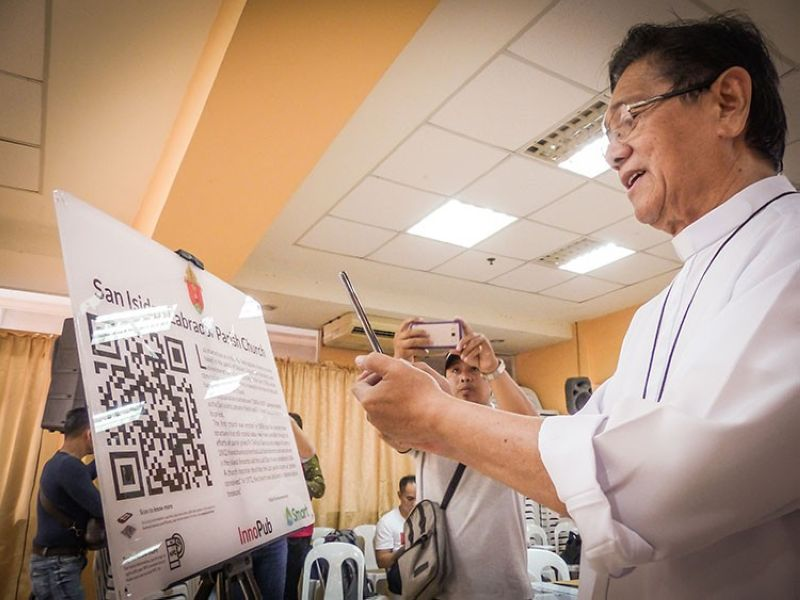 DUMAGUETE. Dumaguete Bishop Julito Cortes scans the QR code for Siquijor's San Isidro Labrador Parish Church or Lazi Church. (Contributed photo)