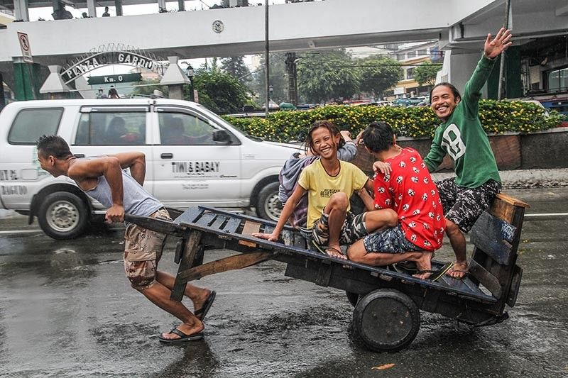 BAGUIO. Despite the rainy weather, a group of porters stays positive as they head back to the public market after delivering fresh vegetables in one of the supermarkets in Baguio City. (Jean Nicole Cortes)
