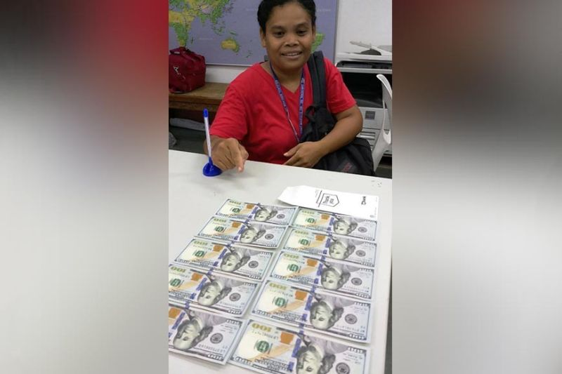 PAMPANGA. Grace Laxamana, 42, shows the money she found at the airport's international departure area. Her honesty was lauded by CIAC president Jaime Melo. (Photo by CIAC)