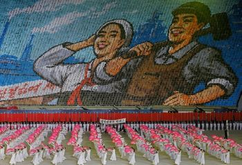 NORTH KOREA. In this Tuesday, July 16, 2019, photo, North Koreans hold cards to make an image depicting a worker and a farmer during a mass game performance of
