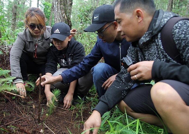 BAGUIO. Family of the late journalist and environmentalist Ramon Dacawi plant trees at the Busol watershed on July 16, 2019. The tree planting was held to commemorate the 1990 killer earthquake and to pay tribute to Baguio City journalists who passed away: Nars Padilla, Domci Cimatu, and Bishop Carlito Cenzon. (Jean Nicole Cortes)
