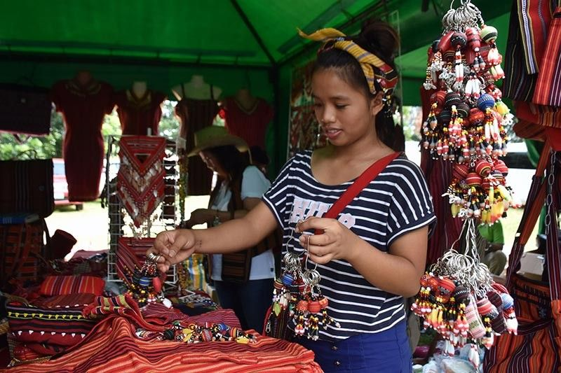 BENGUET. A young Kalinga lass arrange crafts sold as souvenir items during the 32nd Cordillera Day celebration at the Kalinga Sports Complex in Tabuk City, Kalinga last week. (Photo by Redjie Melvic Cawis)