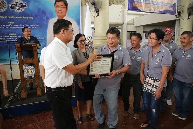 PAMPANGA. Mayor Edwin Santiago awards a certificate to Barangay Pulung Bulu Captain Ernesto Carreon, Jr. and other officials after their barangay was declared drug-cleared by the Regional Oversight Committee on Barangay Drug Clearing Program. (Contributed Photo)