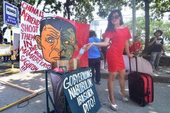 DAVAO. Milabay sa iyang basura ang babayeng nakasuot og pula nga sinina nga adunay dalang maleta susama sa sikat nga meme sa Facebook atol sa gipahigayong protesta sa State of the Nation Address ni Presidente Rodrigo Duterte kung diin gisaysay sa mga progresibong pundok sa ilang rally sa Freedom Park sa Davao City nga basura ang gobyerno. (Macky Lim)