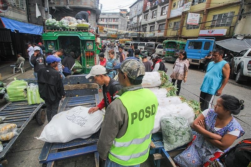 ORDER AT THE MARKET. Personnel of the Peace and Order Safety Division (POSD) closely watch the porters at Kayang Market in Baguio City to ensure the goods being delivered are sold to whole sale buyers since ambulant vendors are strictly prohibited in the city. Violators will have their goods confiscated and will be fined P1,000. Photo by Jean Nicole Cortes