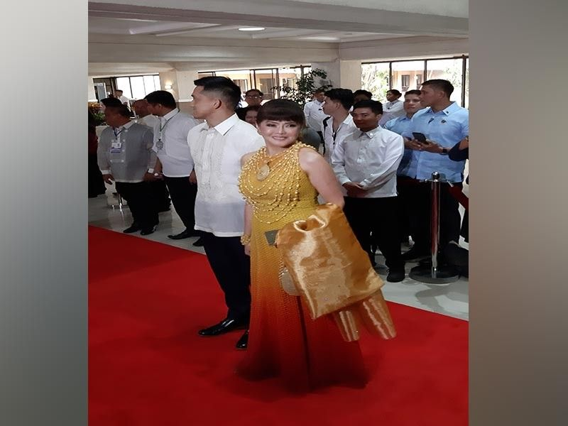 "MANILA. Former President and House Speaker Gloria Macapagal-Arroyo donned a pidayit gown by Kapampangan designer Philip Torres at President Rodrigo Duterte's 4th State of the Nation Address. The gown was inspired by Aetas of Pampanga. Pidayit is a form of upcycling scrap materials. Senator Imee Marcos also walked the red carpet dressed in Mak Tumang, the same designer who won acclaim for his Mayon gown worn by Miss Universe 2019 Catriona Gray during her coronation. Tumang named his creation for Marcos ""La Filigrina"", inspired by Philippine crafts and jewelry, with its gold tambourine swags and medallions accentuating the sunset ombre ""solihiya-inspired"" fabric. The designer added that his creation meant to inspire the viewers ""to look beyond political colors."" (Contributed Photo)"