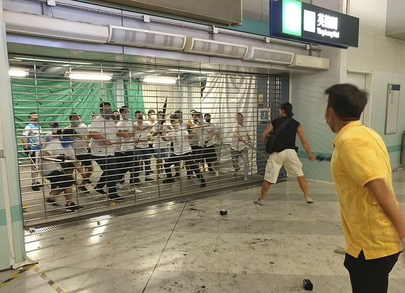 HONG KONG. In this Sunday, July 21, 2019, photo, men in white shirts armed with metal rods and wooden poles attack commuters at a subway station in New Territory in Hong Kong. Hong Kong is reeling after a large gang of men in white shirts brutally beat dozens of people inside a train station in a shocking new twist to the city's summer of protest. (AP)