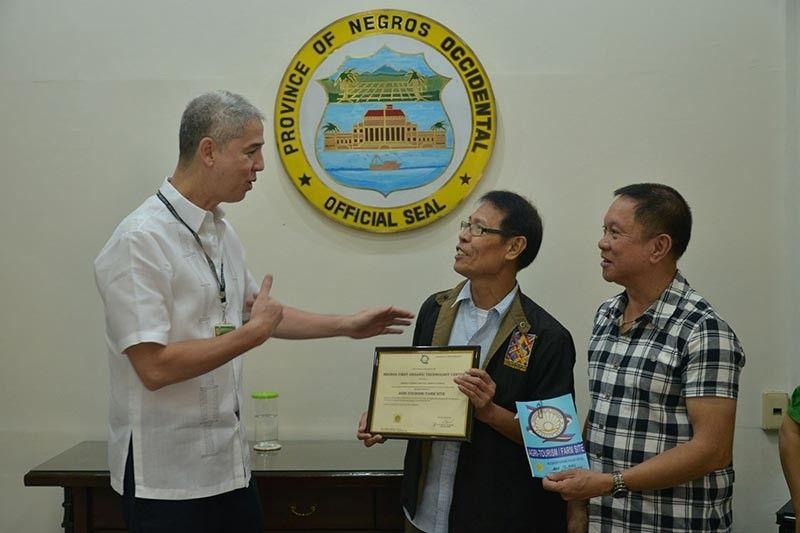 NEGROS OCCIDENTAL. Governor Eugenio Jose Lacson (left) receives the copy of the accreditation from DOT-Western Visayas Regional Administrative Officer Artemio Ticar (center) for the Negros First Organic Technology Center as a farm tourism site at the Provincial Capitol in Bacolod City. Also in photo, Provincial Agriculturist Japhet Masculino. (Capitol photo)