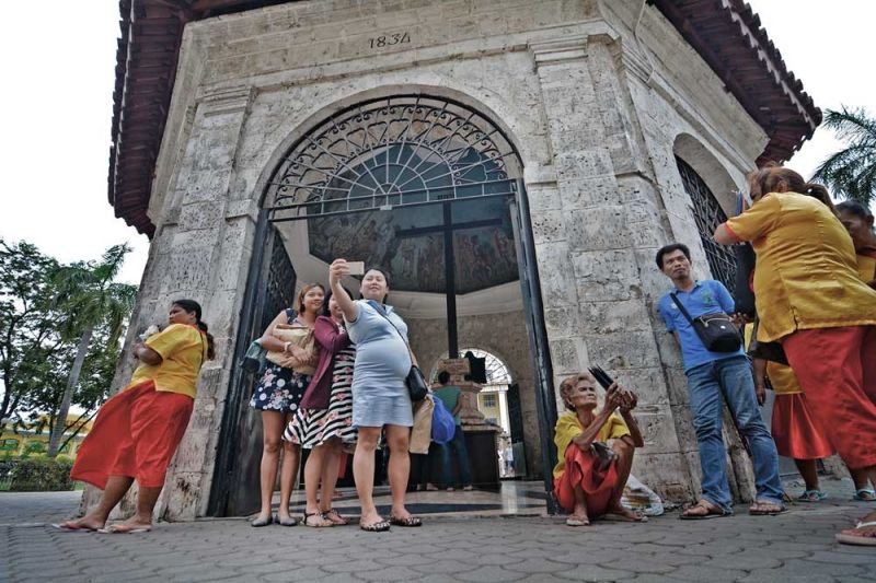 SNAP AND UPLOAD. Visitors take a photo at the Magellan's Cross in Cebu City. The Department of Information and Communications Technology will put up free Wifi sites in popular tourist spots so visitors can instantly upload their photos on the Internet. (SunStar file)