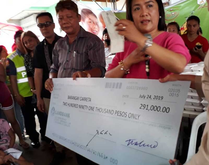 CEBU. Philippine Charity Sweepstakes Office (PCSO) General Manager Royina Garma turns over a check for P291,000 as assistance to fire victims in Barangay Carreta, Cebu City. (SunStar File Photo)