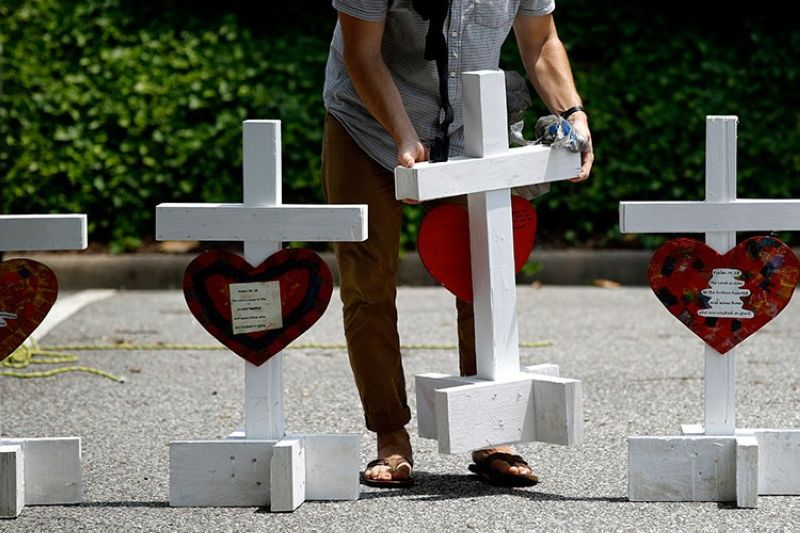 USA. In this June 2, 2019, file photo, a volunteer prepares to place crosses for victims of a mass shooting at a municipal building in Virginia Beach, Virginia, at a nearby makeshift memorial. (AP)